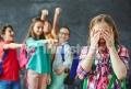 Schoolgirl crying on background of teasing classmates